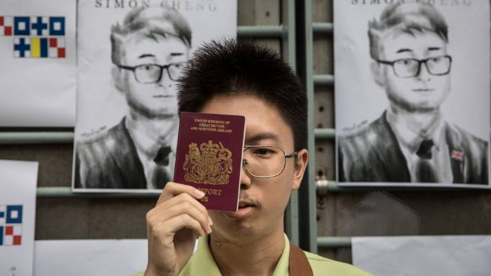 A man holds a UK passport over his face as he stands in front of posters showing a portrait of British consulate worker Simon Cheung as part of a protest while he was missing.