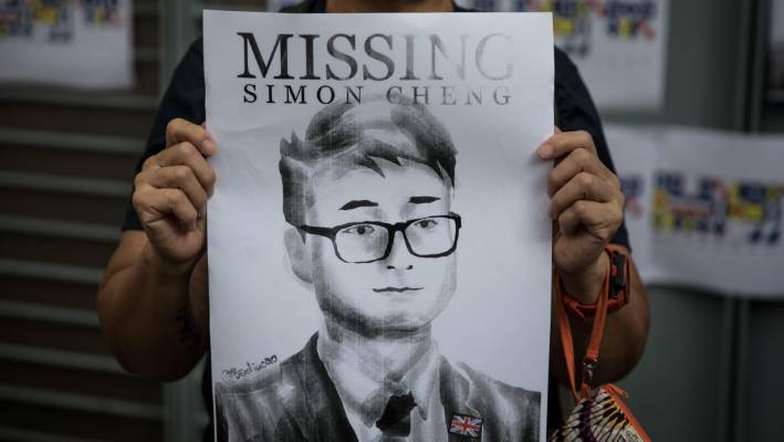 A woman holds a poster showing a portrait of British consulate worker Simon Cheung in August.
