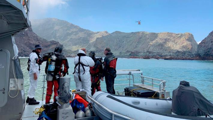 Police divers prepare to search the waters near Whakaari/White Island for missing bodies on Saturday.