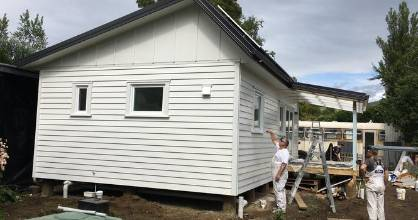 Painters put the finishing touches on the climate safe house.