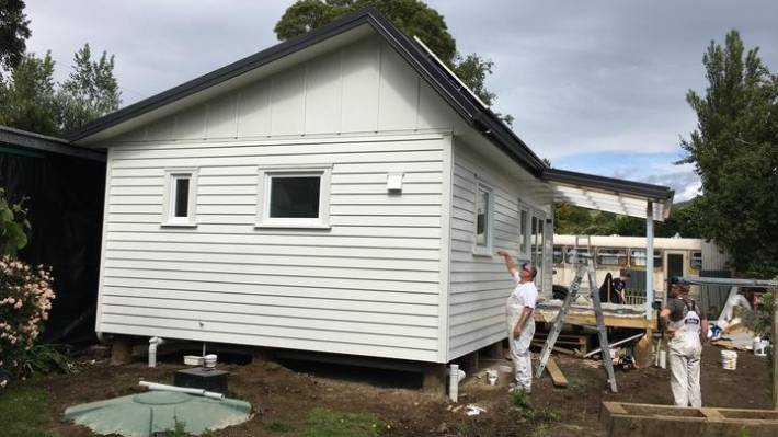 The exterior of the climate safe house as painters put finishing touches on. The home is almost finished and it's hoped it will get sign-off by the end of January.