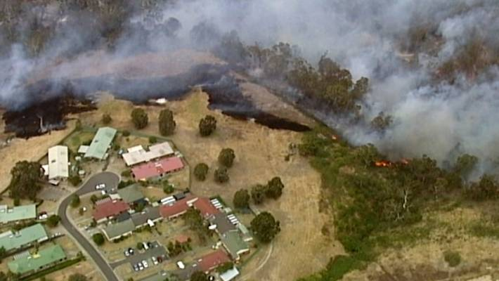 An aerial scene shows fires burning and smoke rising close to properties in Bundoora, Victoria state, December 30, 2019.