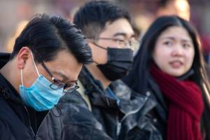 Travellers wear face masks as they walk outside of the Beijing Railway Station. China has reported a sharp rise in the ...
