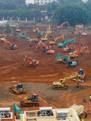 Heavy equipment works at a construction site for a field hospital in Wuhan.