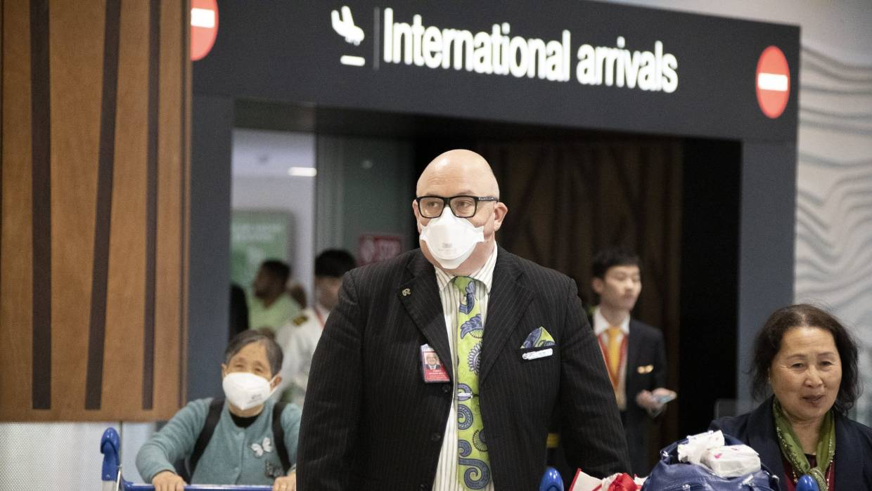 Travellers wearing face masks exiting the arrivals hall at Auckland International Airport. — Photograph: David White.