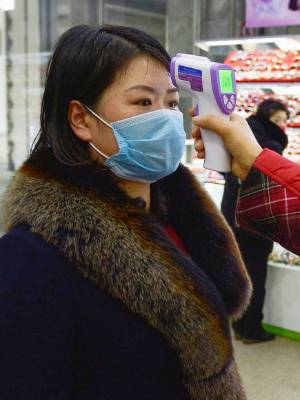 A shopper has their temperature checked at a department store in Pyongyang, North Korea.