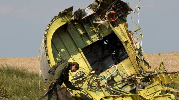A pro-Russian rebel at the MH17 wreckage, near the village of Hrabove, eastern Ukraine, in 2014.