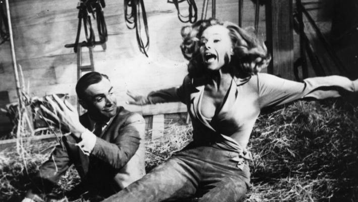 Sean Connery as James Bond up to his tricks with actress Honor Blackman during the filming of  'Goldfinger' at Pinewood studios.