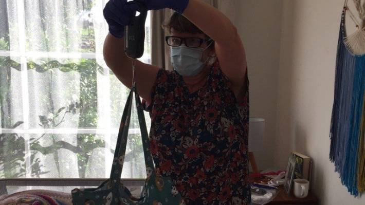 Andrea Sarty wearing Personal Protective Equipment during midwife visits.