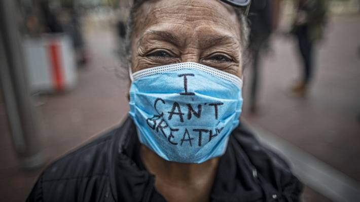 A protestor wears a facemask emblazoned with some last words spoken by US African American man George Floyd, who was killed by a Minnesota police officer.