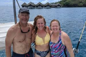 Kristen Pankratz, centre, poses with her parents David and Anne on their yacht Amazing Grace in Tahiti.