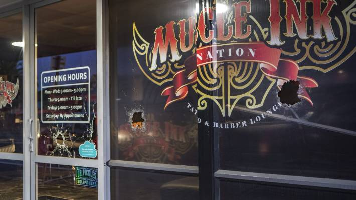 Three bullet holes, which appeared to be from a shotgun, are visible from the front of the tattoo parlour on Wednesday morning.