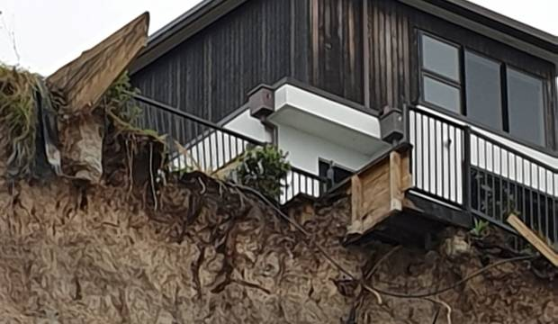 Debris tumbles onto Auckland beach from construction site as cliff edge erodes