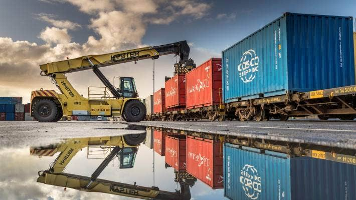 Containers are loaded on rail wagons at Ports of Auckland ,where ships have been waiting up to 17 days to berth.