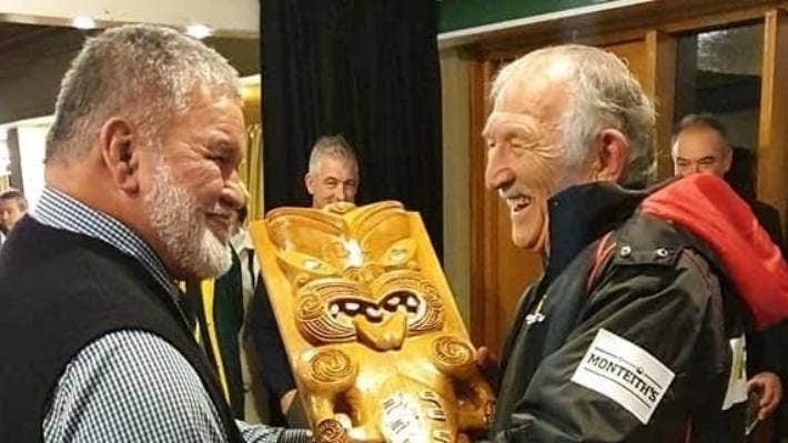 Former All Blacks and Canterbury team-mates Bill Bush (L) and Tane Norton admire a Māori carving created in their honour for a club rugby rivalry in Christchurch.