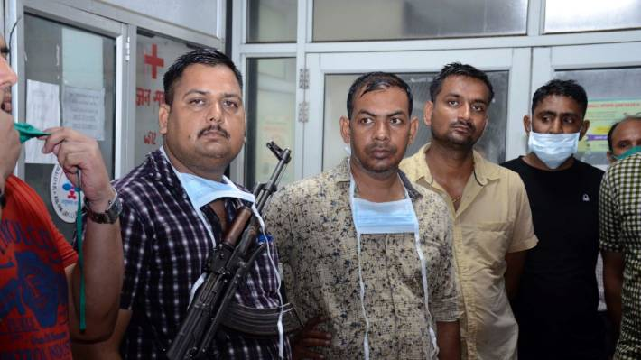 Police officers stand guard at a hospital where the body of Vikas Dubey, a top crime suspect linked to the death of eight policemen was kept in Kanpur, India.
