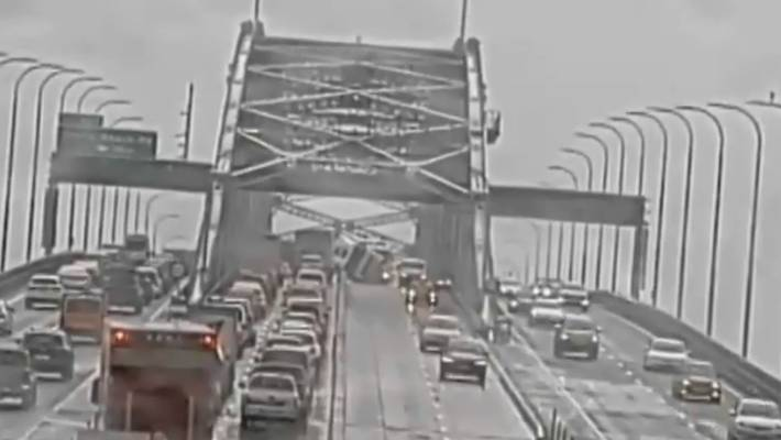 A truck can be seen lying on its side on the Auckland Harbour Bridge.