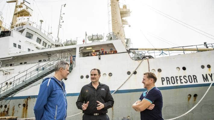 Sealord chief executive Doug Paulin, centre, chats with two of the crew of the Profesor Aleksandrov in October.