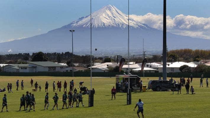 A rugby league match between Te Ati Awa and Ngā Rauru teams is played in Hawera, against a backdrop of Mt Taranaki.