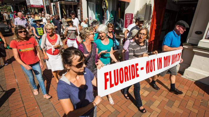 Protesters marching in Nelson during 2017 make their views on fluoridation clear.