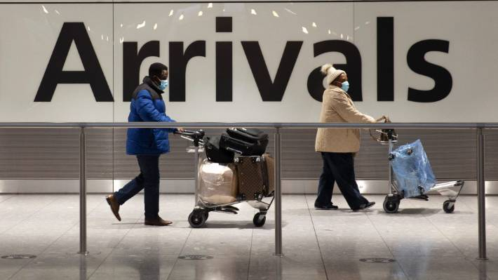 Arriving passengers walk past a sign in the arrivals area at Heathrow Airport in London, Tuesday, Jan. 26, 2021, during England's third national lockdown since the coronavirus outbreak began.