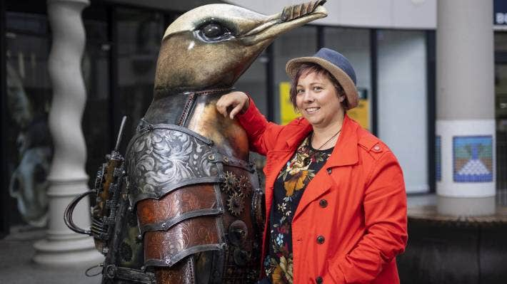 Artist Laura Hewetson with her creation, Punk It Penguin, in Cathedral Junction.