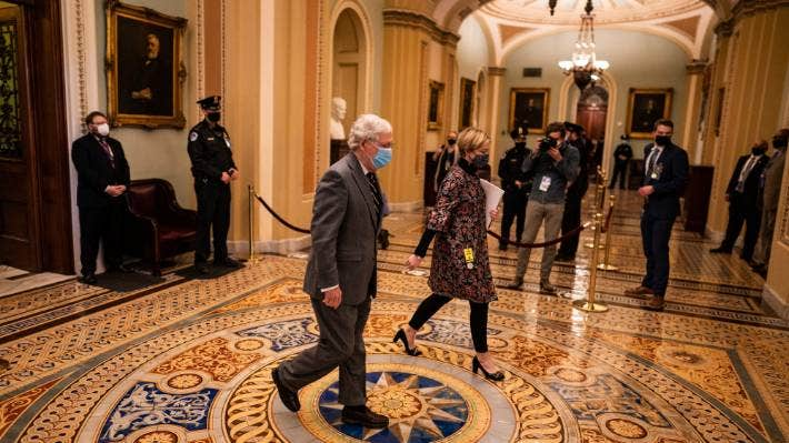 Senate Minority Leader Mitch McConnell walks back to his office as senators take a break during the second day of the impeachment trial.
