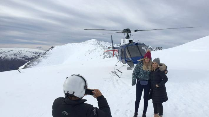 A Helicopter Line pilot photographs Australian tourists near Queenstown after a flight in one of the companies helicopters. (File photo)