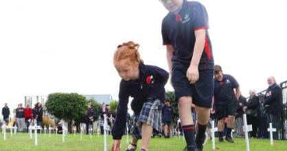 Waiau Area School pupils Peyton Tilby, left, and Cayden Gibbs lay poppies beside the crosses for western Southland ...