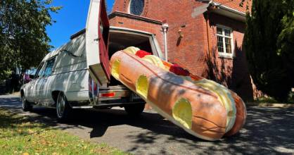This photo provided by Ross Hall, shows a cream doughnut shaped coffin for the funeral of Phil McLean outside a church ...