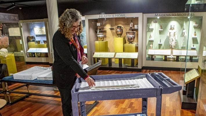 University of Canterbury associate professor Alison              Griffith with the ancient fragment at Christchurch's Teece              Museum of Classical Antiquities.