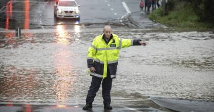 A policeman diverts traffic from a flooded Newlands Rd in July. (File photo)