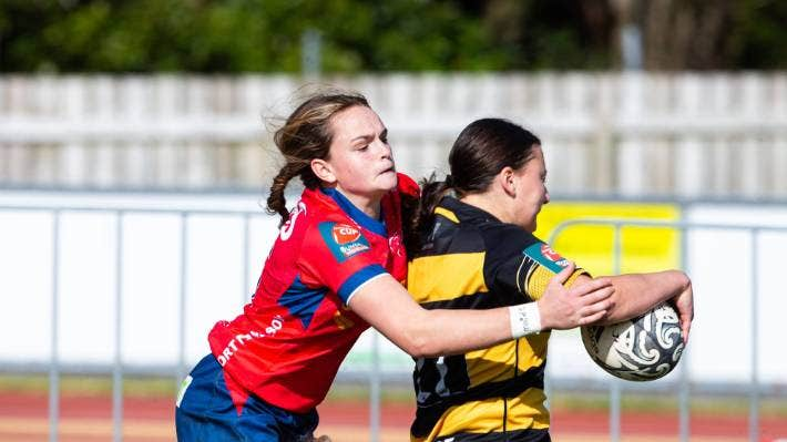 Hannah McLean, of Taranaki Whio, brushing through a tackle as she is about to score.