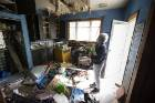 The derelict Thornton St property in Mairehau. TLC Realty's Trish Lawrence in the kitchen.