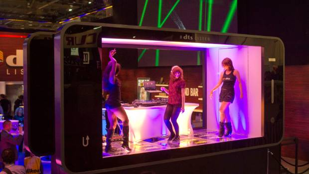 Dancers and a DJ perform in a stage shaped like a giant smartphone at the DTS booth during the 2014 International ...