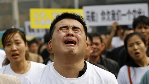 A family member of a passenger on board Malaysia Airlines MH370 cries as he shouts slogans during a protest in front of  ...
