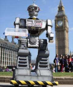 BAN KILLER ROBOTS: A robot distributes promotional literature calling for a ban on fully autonomous weapons in London's ...