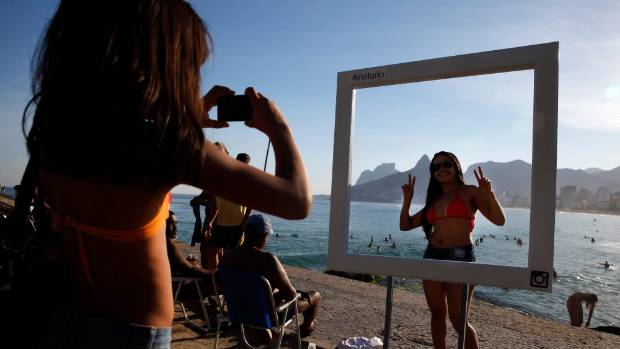 RESIZE: A beachgoer poses for a photo at a suggested Instagram spot on Ipanema Beach, Brazil.