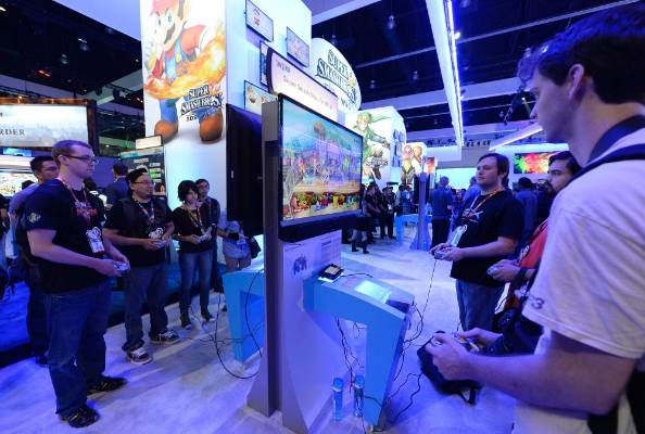 Gamers try out the multiplayer Super Smash Bros at the Nintendo booth at the 2014 Electronic Entertainment Expo.