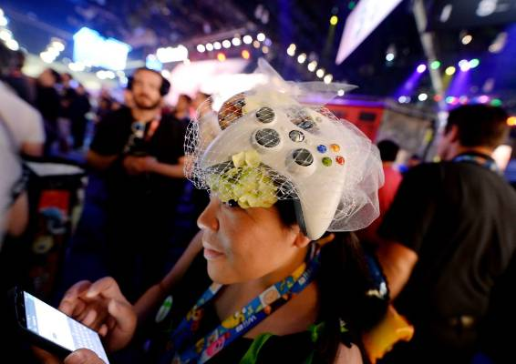 Microsoft employee Sammy Ng wears an Xbox controller as a fascinator as she watches a trailer of the new multiplayer ...