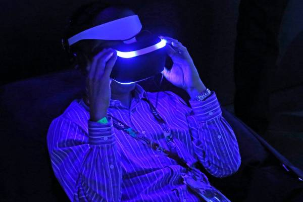 A man adjusts a Sony Project Morpheus virtual reality system at the 2014 Electronic Entertainment Expo.