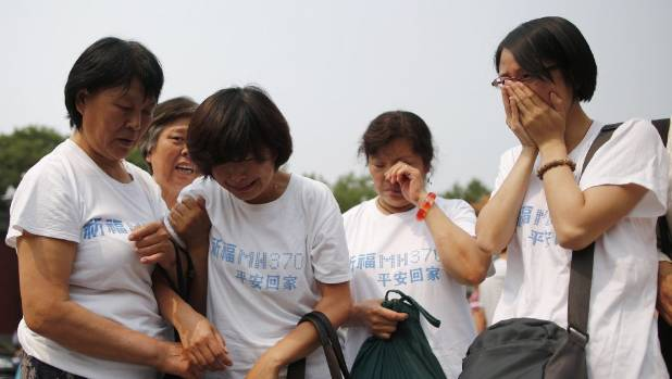 Relatives of passengers aboard the missing jet gather at a Beijing temple in June.