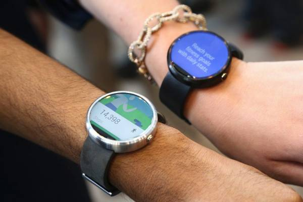 Google employees show off the two different colors of the Moto smartwatch at the Google I/O developers conference.